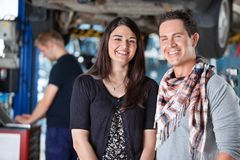 Portrait of smiling young couple in mechanic shop Stock Images