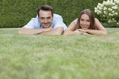 Portrait of smiling young couple relaxing on grass in park Stock Photos