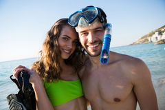 Portrait of smiling young couple with scuba mask at beach Royalty Free Stock Photo