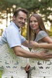 Portrait of smiling young couple sitting on chairs in park Royalty Free Stock Images