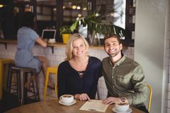 Smiling young couple sitting with coffee and menu at table in cafe Royalty Free Stock Images