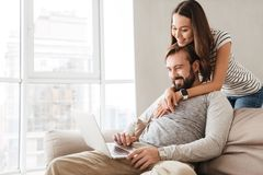Portrait of a smiling young couple using laptop computer. While hugging at home on a couch Stock Photography
