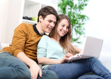 Portrait of a smiling young couple using laptop at home indoor Stock Image
