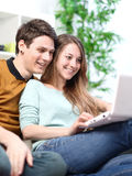 Portrait of a smiling young couple using laptop at home indoor Stock Photography
