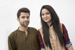 Portrait of smiling young couple wearing traditional clothing from Pakistan, studio shot Stock Image
