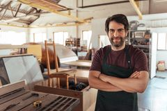 Smiling woodworker standing by a bench saw in his workshop Stock Images