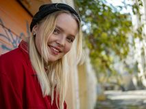Portrait of smiling young cute girl in knitted hat outdoors standing near the wall stock photo