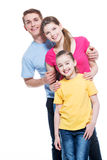 Portrait of the smiling young family with child. Portrait of the smiling young family with kid in multicolor shirts - isolated on white background stock images
