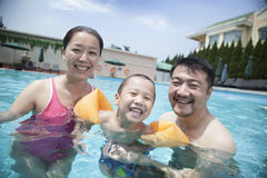 Portrait of smiling young family in the pool on vacation Stock Photos