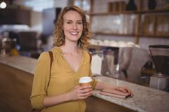 Portrait of smiling young female customer holding disposable coffee cup at counter Stock Images