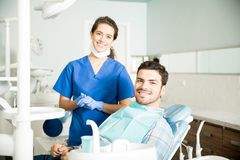 Portrait Of Smiling Dentist And Mid Adult Man In Clinic. Portrait of smiling young female dentist standing by mid adult men in clinic stock photo