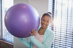 Portrait of smiling young female doctor holding purple exercise ball. At hospital ward Stock Image