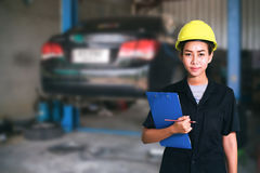 Portrait of smiling young female mechanic inspecting on a car in Stock Photos