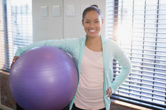 Portrait of smiling young female physiotherapist holding purple exercise ball Royalty Free Stock Photos