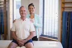 Portrait of smiling young female physiotherapist standing by male patient sitting on bed Royalty Free Stock Photography
