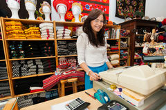 Portrait of smiling young female salesperson at checkout stand in gift store Stock Image