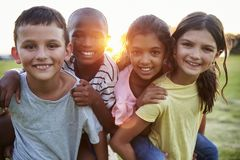 Portrait of smiling young friends piggybacking outdoors Stock Images