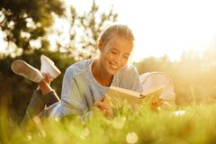 Portrait of a smiling young girl with backpack. Laying on a grass at the park, reading a book Stock Photo
