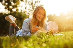 Portrait of a smiling young girl with backpack. Laying on a grass at the park, reading a book Royalty Free Stock Photography