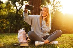 Portrait of a smiling young girl with backpack. Sitting on a grass at the park, taking selfie Royalty Free Stock Image