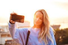 Portrait of a smiling young girl with backpack. Standing outdoors during sunset, taking selfie with mobile phone Stock Photo