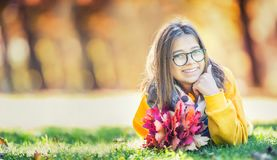 Portrait of a smiling young girl with bouquet of maple leaves. royalty free stock image