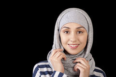 Portrait of a smiling young girl eastern appearance, with his head covered in a Muslim-style on a black background Royalty Free Stock Images