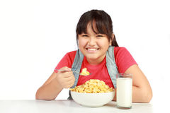 Portrait of smiling young girl having breakfast Royalty Free Stock Photo
