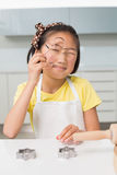 Portrait of a smiling young girl holding cookie mold in kitchen Royalty Free Stock Photo