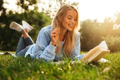 Portrait of a smiling young girl with backpack. Portrait of a smiling young girl laying on a grass at the park, reading a book, taking notes Royalty Free Stock Images