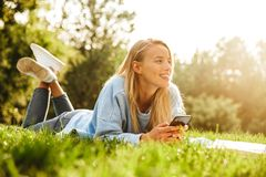 Portrait of a smiling young girl laying on a grass at the park. Using mobile phone Royalty Free Stock Image