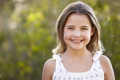 Portrait of smiling young girl looking to camera outdoors Stock Images