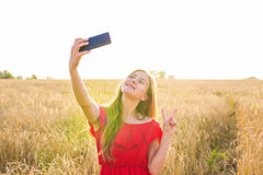Portrait of a smiling young girl making selfie photo in the field Royalty Free Stock Images