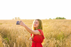 Portrait of a smiling young girl making selfie photo in the field Stock Images
