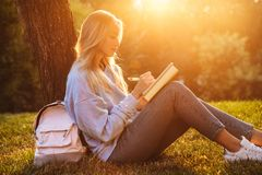 Portrait of a smiling young girl sitting on a grass. At the park, reading a book, taking notes Stock Image