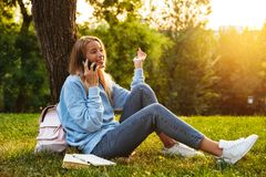 Portrait of a smiling young girl sitting on a grass. At the park, talking on mobile phone Royalty Free Stock Images