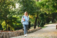Portrait of a smiling young girl student with backpack. And textbook walking at the park Royalty Free Stock Image