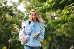 Portrait of a smiling young girl student with backpack. And textbook walking at the park, talking on mobile phone Stock Images
