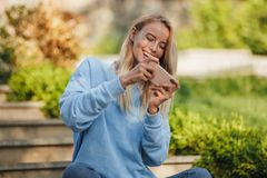Portrait of a smiling young girl student sitting. On steps outdoors, playing games on mobile phone Royalty Free Stock Photo