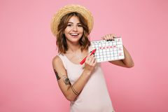 Portrait of a smiling young girl in summer hat. Checking her periods according to calendar isolated over pink background Stock Photo