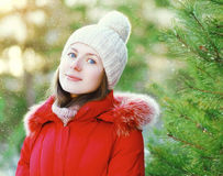 Portrait smiling young girl wearing a red jacket and hat in winter day Stock Photos