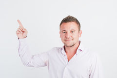 Portrait of smiling young guy pointing upwards Royalty Free Stock Photo