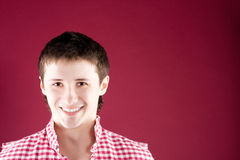 Portrait of a smiling young guy on red Stock Photo