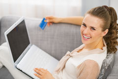 Portrait of smiling young housewife with credit card and laptop Stock Images