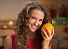 Portrait of smiling young housewife with orange in kitchen Stock Images