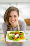 Portrait of smiling young housewife showing salad Stock Photo