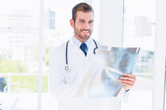 Portrait of a smiling young male doctor examining xray Stock Images