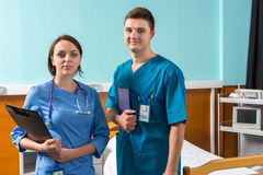 Portrait of smiling young male and female doctor in uniform with. Phonendoscope on her neck holding clipboards while standing in the hospital ward. Healthcare Royalty Free Stock Photo