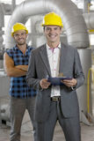 Portrait of smiling young male manager holding clipboard with worker in background at industry Stock Images