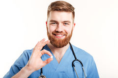 Portrait of a smiling young male medical doctor or nurse. Holding a pill capsule on white background Royalty Free Stock Photo